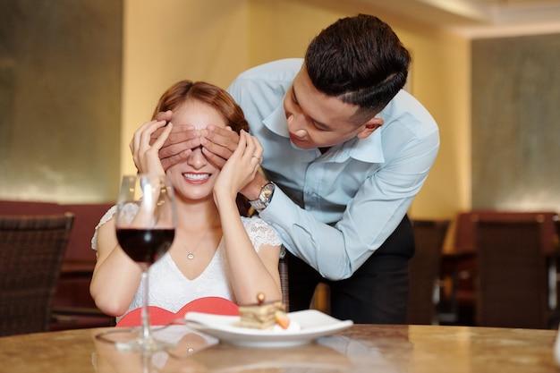 高級レストランでガールフレンドのためにロマンチックな驚きを作る若い男