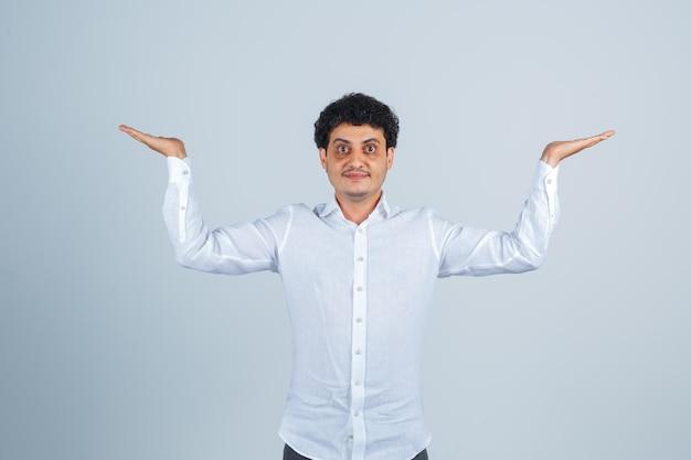 젊은 남자는 흰 셔츠에 비늘 몸짓을 하고 자신감 있고 앞모습을 보고 있습니다.