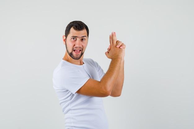 Giovane che fa il gesto di tiro in maglietta e che sembra coraggioso. vista frontale.