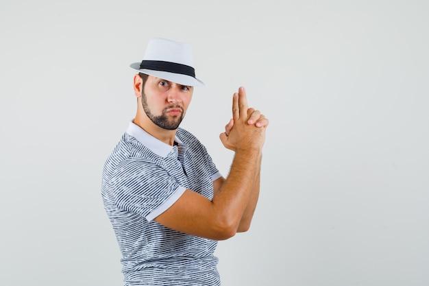 Молодой человек делает жест стрельбы из пистолета в полосатой футболке, шляпе и выглядит храбрым. передний план.