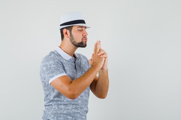 Молодой человек делает жест стрельбы из пистолета в полосатой футболке, шляпе и выглядит сосредоточенным. передний план.