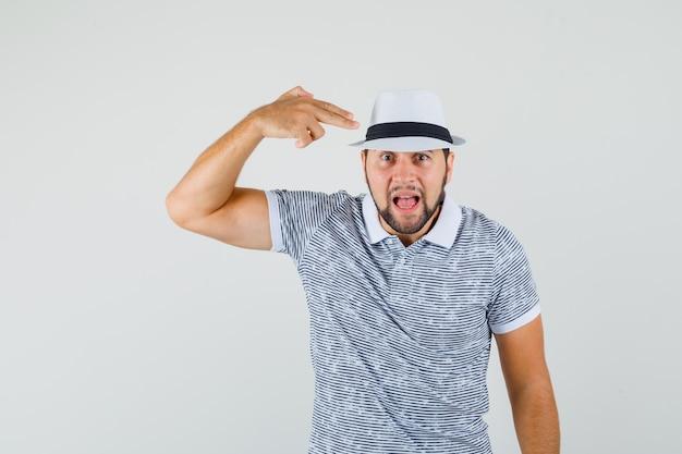 Молодой человек делает жест стрельбы из пистолета над головой в полосатой футболке, шляпе и выглядит испуганным. передний план.