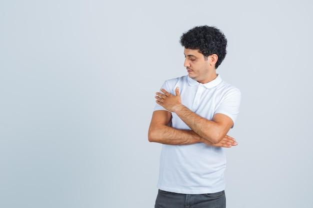 Молодой человек делает жест превосходства, вытирая плечо в белой футболке, брюках и выглядит элегантно, вид спереди.
