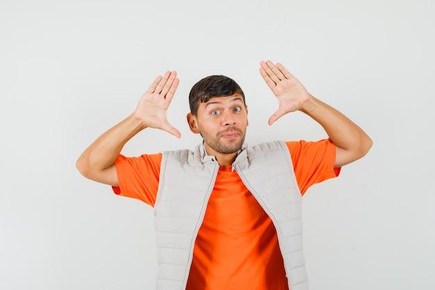 Tシャツ、ジャケット、正面図で降伏ジェスチャーをする若い男。