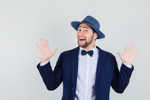 Giovane che fa gesto di resa in vestito, cappello e che sembra allegro. vista frontale.