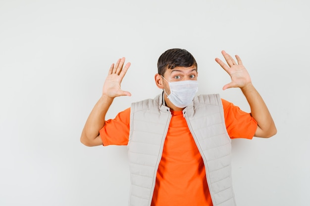 Young man making surrender gesture in t-shirt, jacket, mask front view.