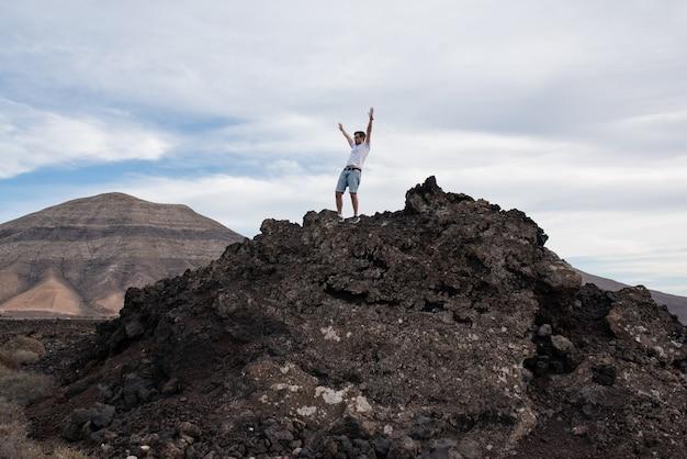 山の頂上で勝利のジェスチャーをしている若い男。