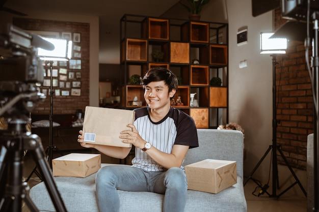 Молодой человек делает распаковку обзорной записи видео для влог