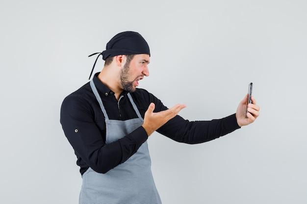 젊은 남자 셔츠, 앞치마에 휴대 전화에 화상 통화를하고 분노, 전면보기를 찾고.