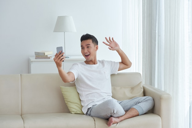 Young man making a video call sitting on the sofa in his living room and giving a greeting wave gesture