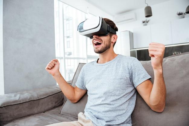 Молодой человек делает жест победителя, нося устройство виртуальной реальности и сидя на диване.