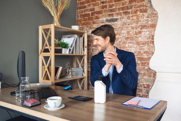 若い男、マネージャー、チームは検疫後に彼のオフィスで仕事に戻るように導き、幸せを感じています
