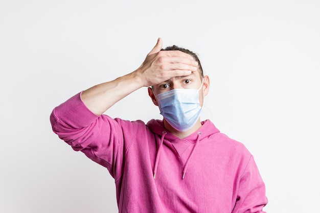 Young man in mask and magenta color hoodie measures temperature with hand on white wall portrait of handsome male model with brown eyes and hear.