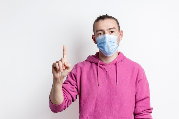 Young man in mask and magenta color hoodie pointing up on white wall portrait of handsome male model with brown eyes and hear.