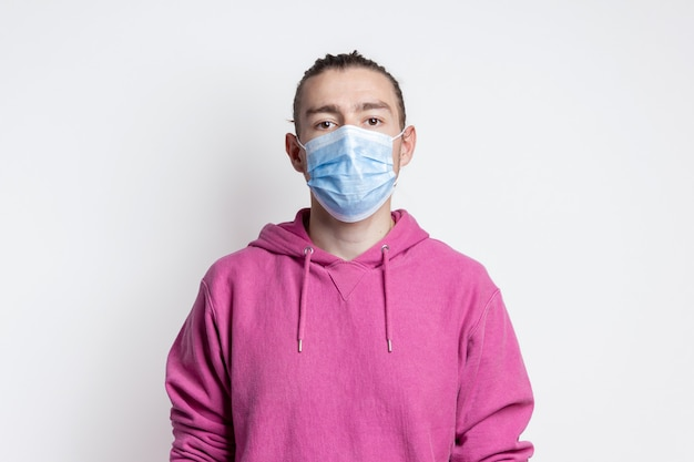 Young man in mask and magenta color hoodie on white wall.portrait of handsome male model with brown eyes and hear.