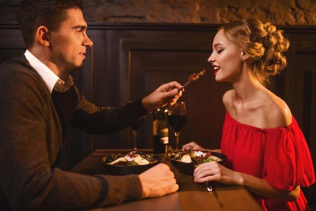 若い男はレストランで赤いドレスを着たエレガントな女性を食事します。一緒に美しい愛のカップルの楽しみ、ロマンチックな夜