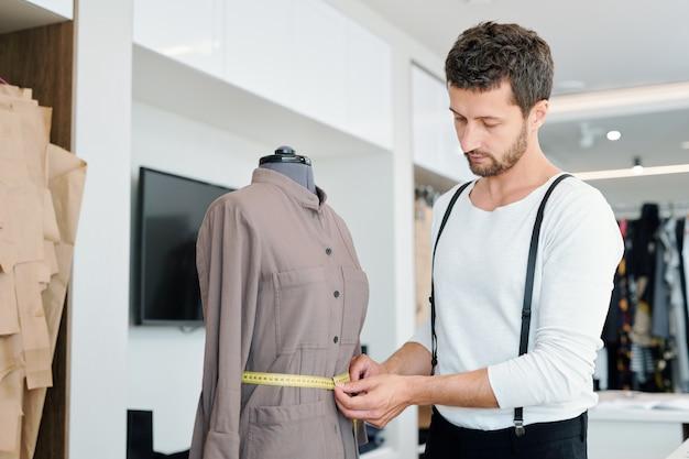 Молодой человек измеряет талию женской куртки на манекене, работая над новым заказом клиента