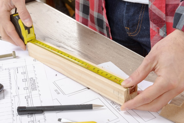 Young man measuring wooden board
