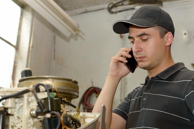 Young man mechanic repairing motor boats and phone at customer