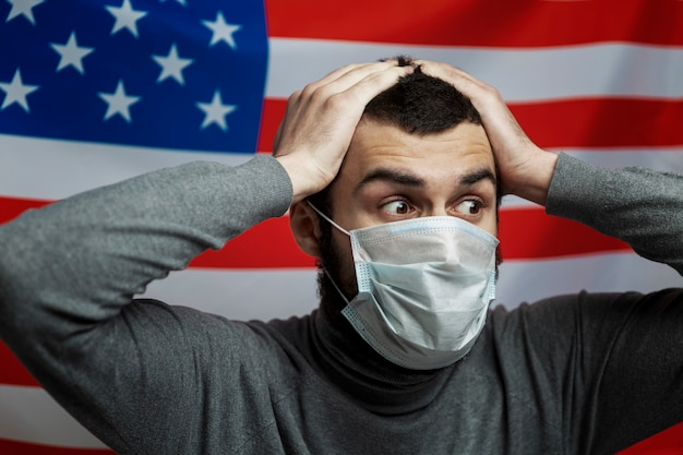 Young man in a medical mask on the background of the american flag. holds hands shcha head in horror. close-up.