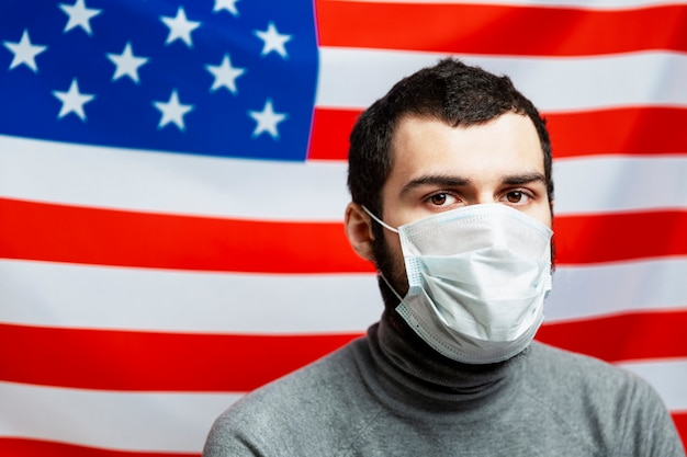 Young man in a medical mask on the background of the american flag. independence day, a period of unrest and pandemic of the coronavirus close-up.