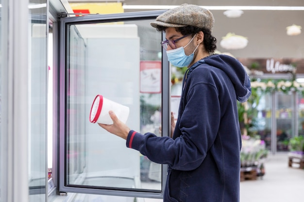 A young man in a medical mask chooses frozen food in a supermarket