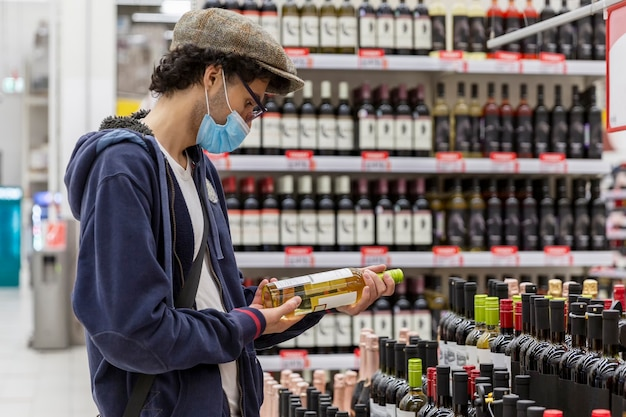 A young man in a medical mask chooses wine in a supermarket