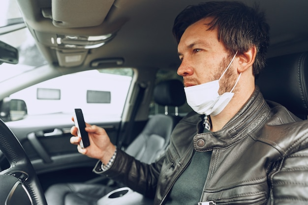 Young man in medical mask using smartphone in car