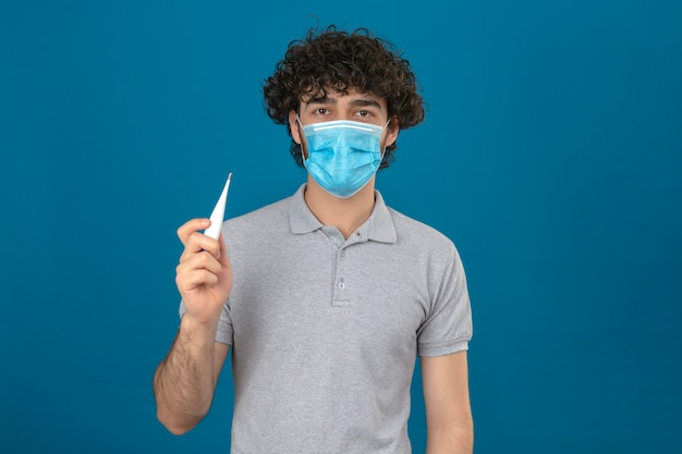 Young man in medical protective mask holding digital thermometer in hand looking at camera with serious face over isolated blue background
