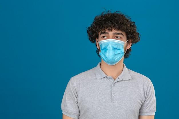 Giovane in mascherina protettiva medica che osserva da parte con la faccia seria che sta sopra fondo blu isolato
