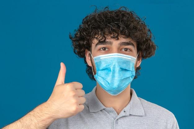 Giovane uomo in maschera protettiva medica che guarda l'obbiettivo con la faccia felice che mostra il pollice in su su sfondo blu isolato
