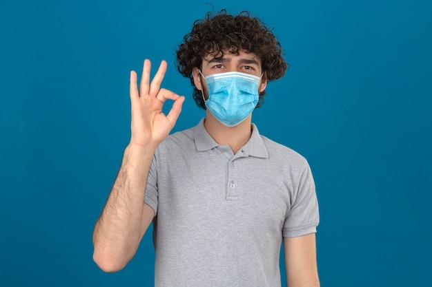 Giovane uomo in mascherina protettiva medica che guarda l'obbiettivo con il sorriso che fa segno giusto sopra fondo blu isolato