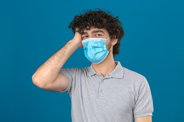 Giovane uomo in maschera protettiva medica cercando confuso toccando la testa nessun concetto di idea in piedi su sfondo blu isolato