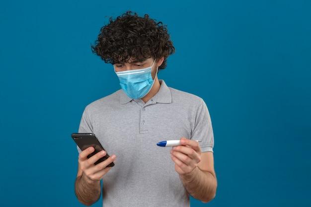 Giovane uomo in maschera protettiva medica guardando lo schermo del suo smartphone tenendo il termometro digitale in altra mano cercando nervoso su sfondo blu isolato