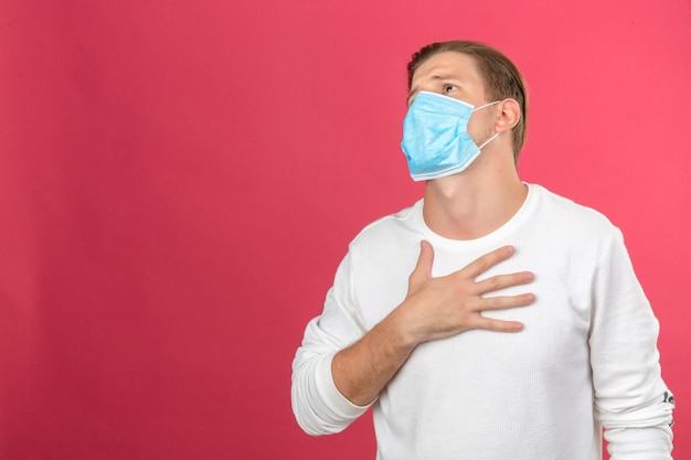 Young man in medical protective mask looking sick and frightened touching his chest over isolated pink background with copy space