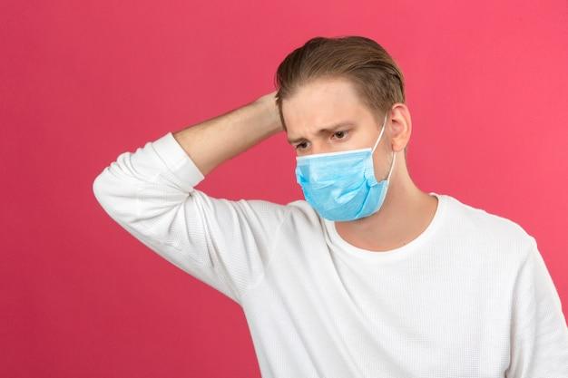 Giovane uomo in maschera protettiva medica cercando malati toccando la testa in piedi su sfondo rosa isolato