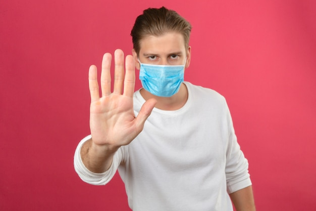 Young man in medical protective mask making stop sign with hand looking at camera with serious face standing over isolated pink background