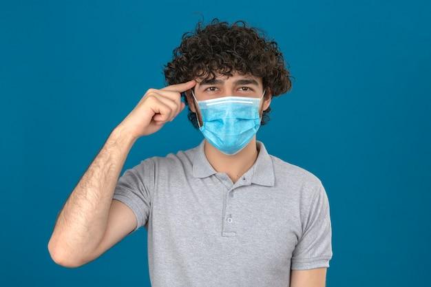 Giovane uomo in maschera protettiva medica che punta il tempio con il dito pensando focalizzato su un compito su sfondo blu isolato