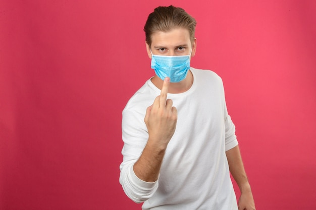 Giovane uomo in mascherina protettiva medica che mostra il dito medio espressione maleducata su sfondo rosa isolato