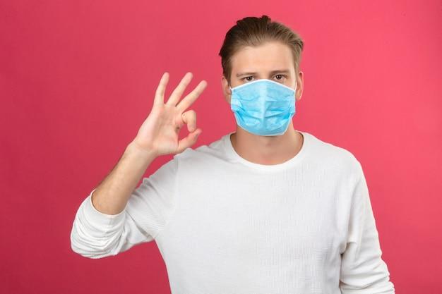 Giovane uomo in mascherina protettiva medica che mostra segno ok con le dita e la mano che guarda l'obbiettivo su sfondo rosa isolato