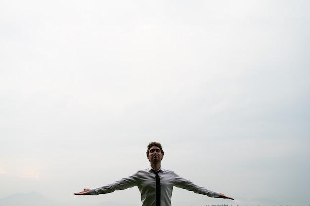 Young man meditating under cloudy sky