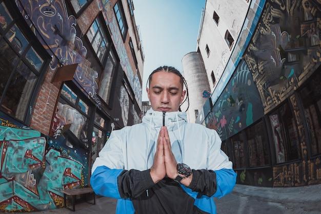 通りで瞑想する若い男