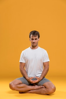 Young man meditating in lotus pose