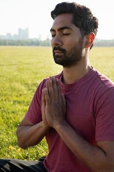 Молодой человек медитирует на открытом воздухе