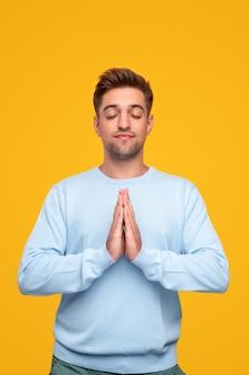 Молодой человек медитирует со сложенными руками