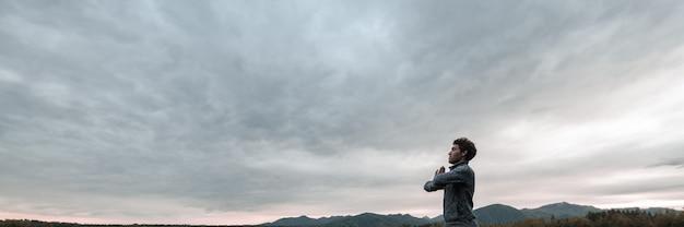Молодой человек медитирует, сложив руки на груди, стоя под мистическим вечерним небом.