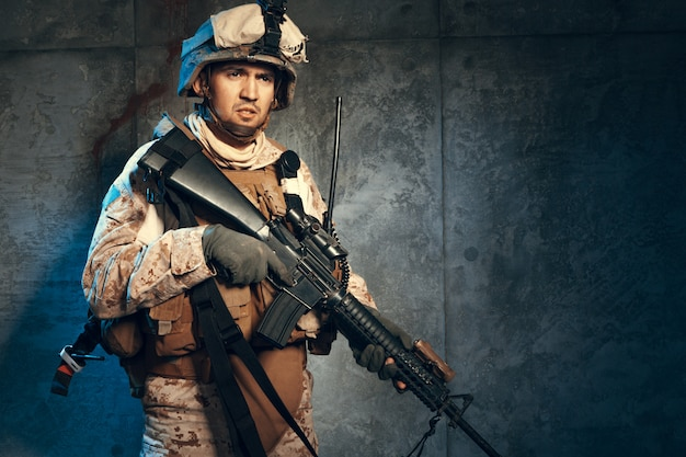 Young man in military outfit a mercenary soldier in modern times on a dark background in studio