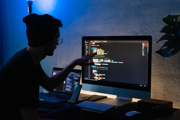 Young man mobile developer writes program code on a computer, programmer work in home office.
