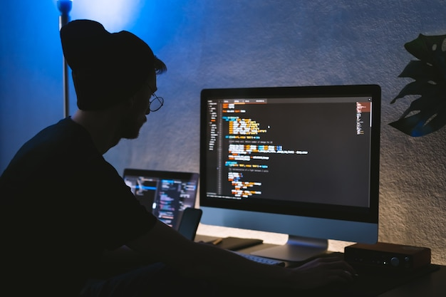 Молодой человек мобильный разработчик пишет программный код на компьютере, программист работает в домашнем офисе.