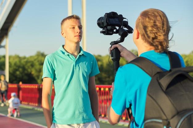 若い男性モデルと男性オペレーターがカメラとスタビライザーで写真ビデオを撮る